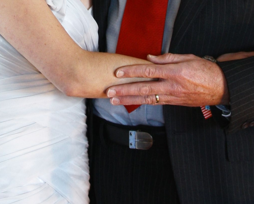 A father's hand kissing the bride
